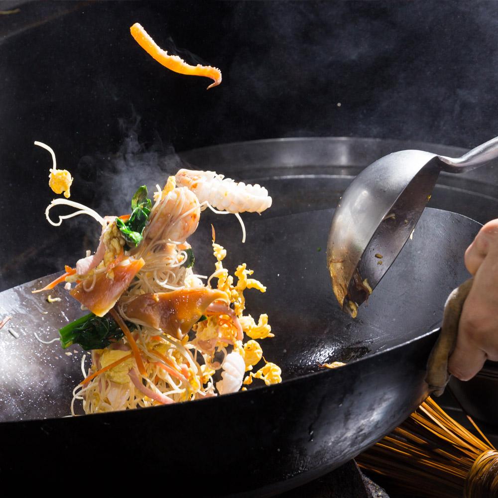 mise en avant de la cuisine traditionnelle avec une sauteuse tenue par un cuisinier en action