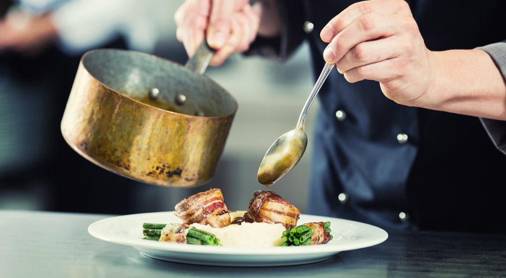 cuisine traditionnelle avec une assiettes de viande en sauce, le cuisinier fait les finitions du plat