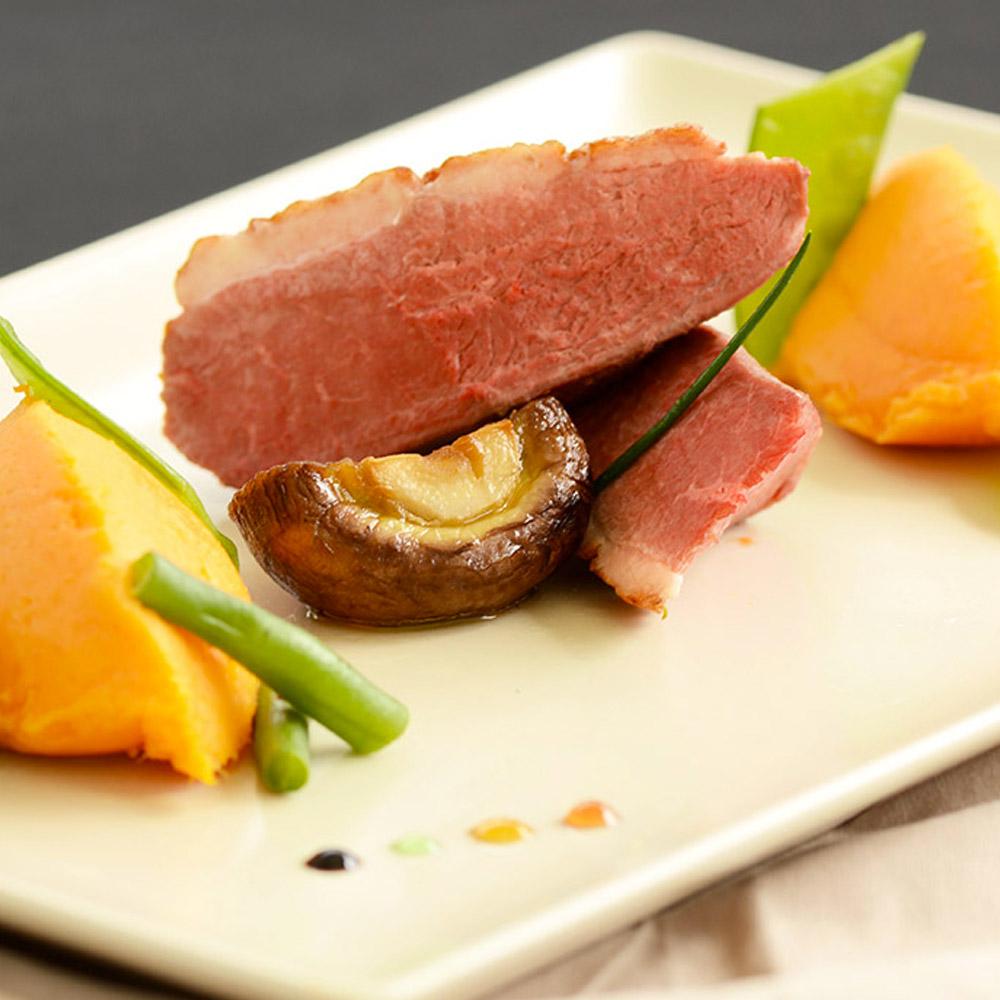 présentation d'un plat de viande : canard rosé accompagné d'une purée de carottes et sa garniture